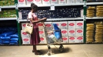 A woman does a quick calculation on her phone before buying groceries at a shop in Harare, in this Wednesday, Oct, 9, 2019 photo. (AP Photo/Tsvangirayi Mukwazhi)