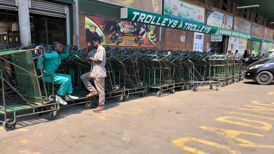 Vendors who make a living from pushing customer trollies, wait for customers outside a supermarket in Harare, in this Wednesday, Oct, 9, 2019 photo. Hyperinflation is changing prices so quickly in the southern African nation that what you would see displayed on a supermarket shelf might change by the time you reach the checkout. (AP Photo/Tsvangirayi Mukwazhi)