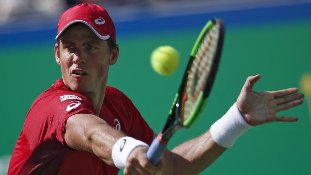 Pospisil hits a return shot against Medvedev