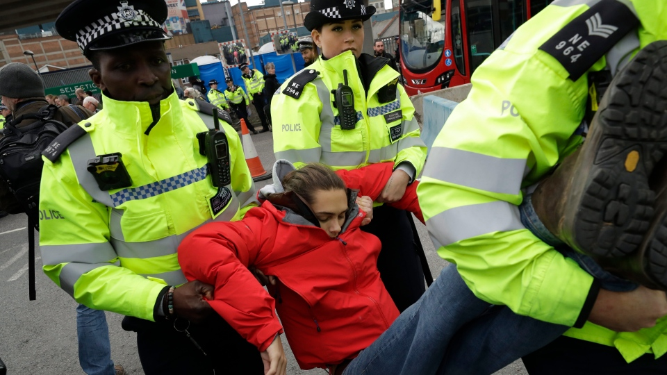 An Extinction Rebellion climate change protester is removed by police from blocking a road outside City Airport in London, Thursday, Oct. 10, 2019. (AP Photo/Matt Dunham)