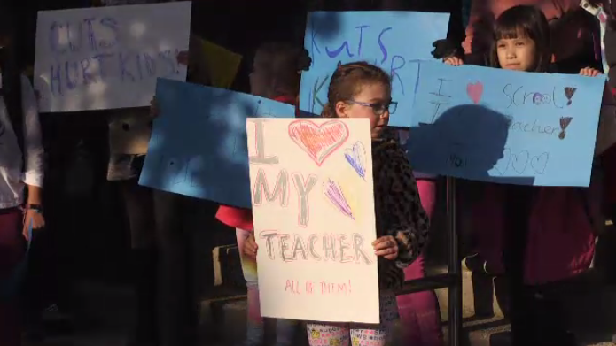 "A young student holds a sign that reads ""I (heart) my teacher"" at a walk-in supporting education workers."