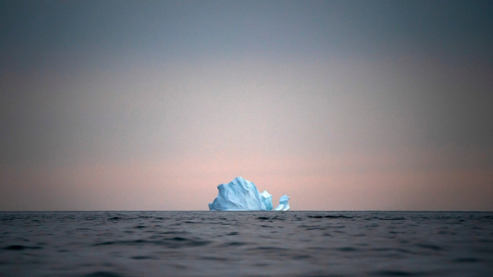 In this Aug. 15, 2019, photo, a large iceberg floats away as the sun sets near Kulusuk, Greenland. THE CANADIAN PRESS/AP/Felipe Dana