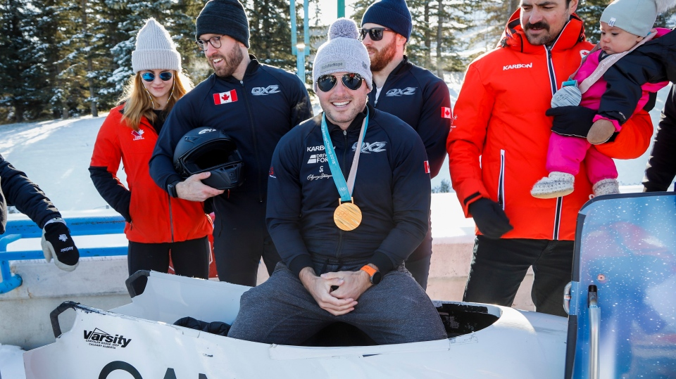 Justin Kripps, centre, Olympic bobsleigh champion, and other bobsleigh, skeleton and luge athletes gather at the finish line of the Olympic Track in Calgary, Alta., Thursday, Oct. 10, 2019, in an effort to showcase the positive impact the facility has had on the city, province and country. THE CANADIAN PRESS/Jeff McIntosh
