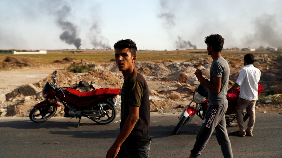 People in Akcakale, Sanliurfa province, southeastern Turkey, at the border with Syria, watch smoke billowing from targets inside Syria, during bombardment by Turkish forces, Thursday, Oct. 10, 2019. (AP Photo/Lefteris Pitarakis)