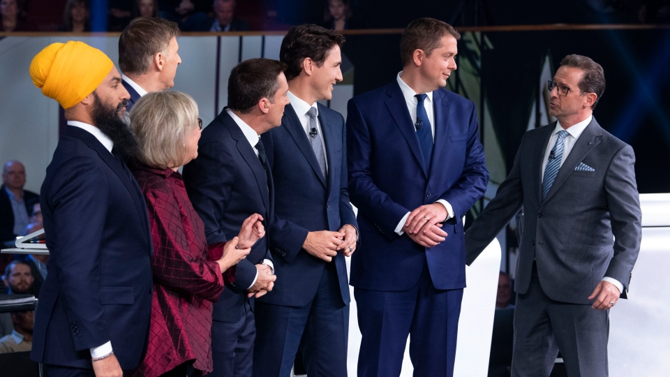 Host Patrice Roy from Radio-Canada, centre, introduces Federal party leaders, left to right, NDP leader Jagmeet Singh, Green Party leader Elizabeth May, People's Party of Canada leader Maxime Bernier, Liberal leader Justin Trudeau, Conservative leader Andrew Scheer, and Bloc Quebecois leader Yves-Francois Blanchet before the Federal leaders french language debate in Gatineau, Que. on Thursday, October 10, 2019. (THE CANADIAN PRESS/Adrian Wyld)