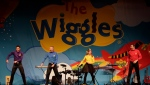 In this Sunday, July 21, 2013 photo, The Wiggles' from left, Lachy, Anthony Emma and Simon dance on stage during a performance in Canberra, Australia. (AP Photo/Rob Griffith)