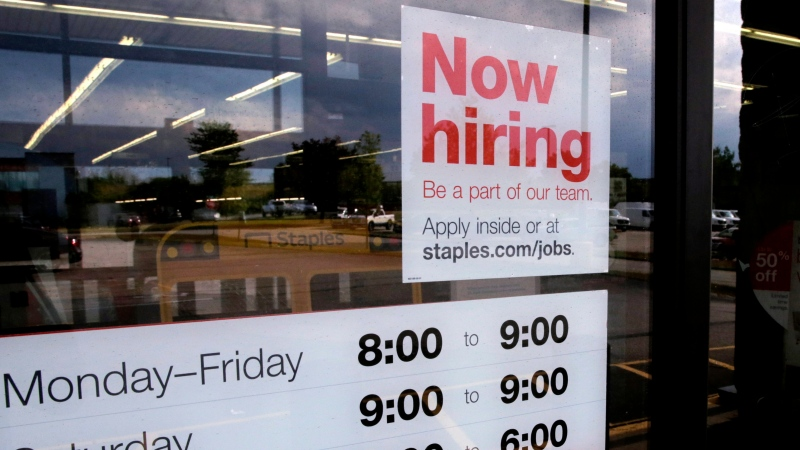 "In this Aug. 15, 2019, file photo a ""Now hiring"" sign is displayed on the front door of a Staples store.(AP Photo/Charles Krupa, File)"