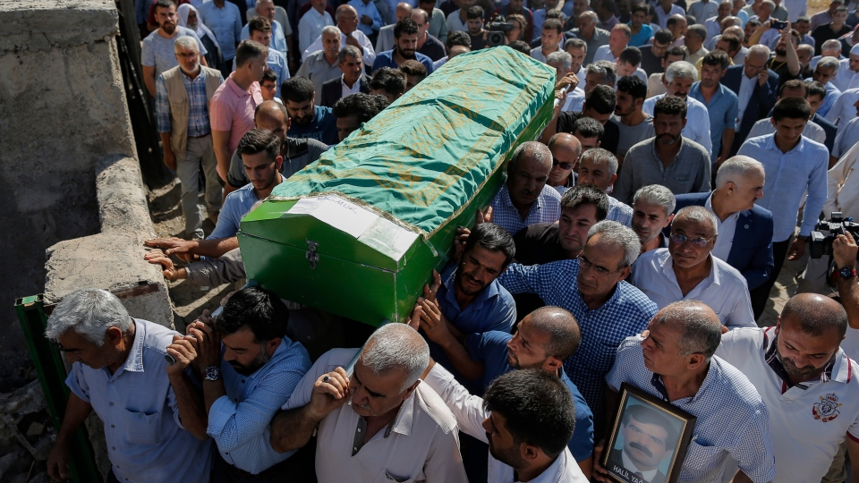 Mourners carry the coffin of Halil Yagmur, 64 killed Friday during mortar shelling from Syria, during a funeral procession in the town of Suruc, southeastern Turkey, at the border with Syria, Saturday, Oct. 12, 2019. . (AP Photo/Emrah Gurel)