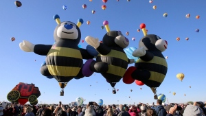 Spectators watch as hot air balloons liftoff at the Albuquerque International Balloon Fiesta in Albuquerque, N.M., Sunday, Oct. 6, 2019. (Jerry Larson/Waco Tribune-Herald via AP)