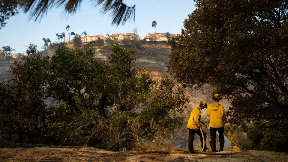 Los Angeles County firefighters work hot spots in the Porter Ranch area of Los Angeles, on Friday, Oct. 11, 2019, after the Saddleridge Fire burned through thousands of acres during Santa Ana wind conditions. (Sarah Reingewirtz/The Orange County Register/SCNG via AP)