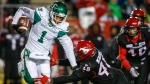 Saskatchewan Roughriders' Shaquelle Evans, left, escapes a tackle from Calgary Stampeders' Wynton McManis during second half CFL football action in Calgary, Friday, Oct. 11, 2019.THE CANADIAN PRESS/Jeff McIntosh