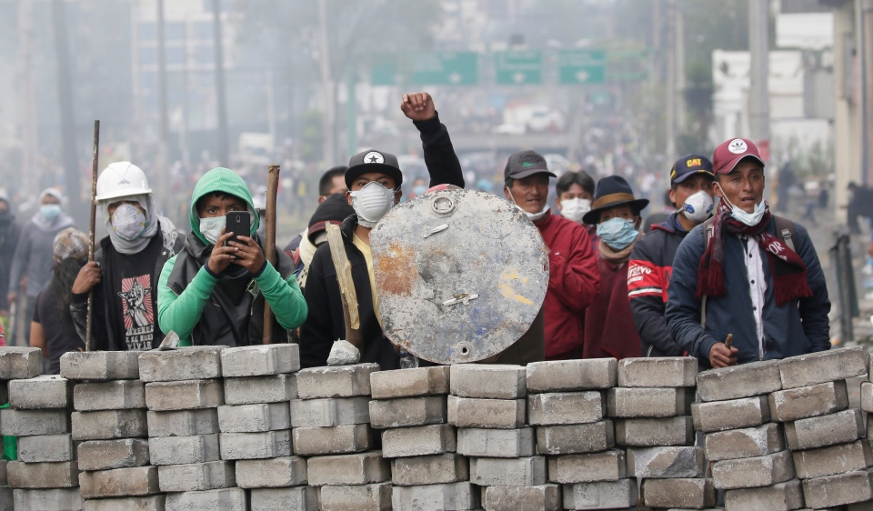 Anti-government demonstrators man a barricade during clashes with the police, near the national assembly building in Quito, Ecuador, Saturday, Oct. 12, 2019. Indigenous leaders of protests that have paralyzed Ecuador's economy for nearly a week say they are willing to negotiate with President Lenin Moreno, signaling a possible exit from the crisis, which was triggered by the cancellation of fuel subsidies by Moreno. (AP Photo/Dolores Ochoa)