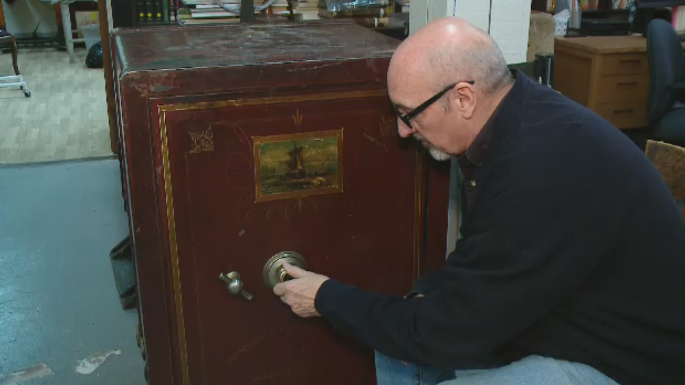 Rob Deglau inspects a nearly-century old safe that the Civic Museum of Regina is trying to crack the code for.