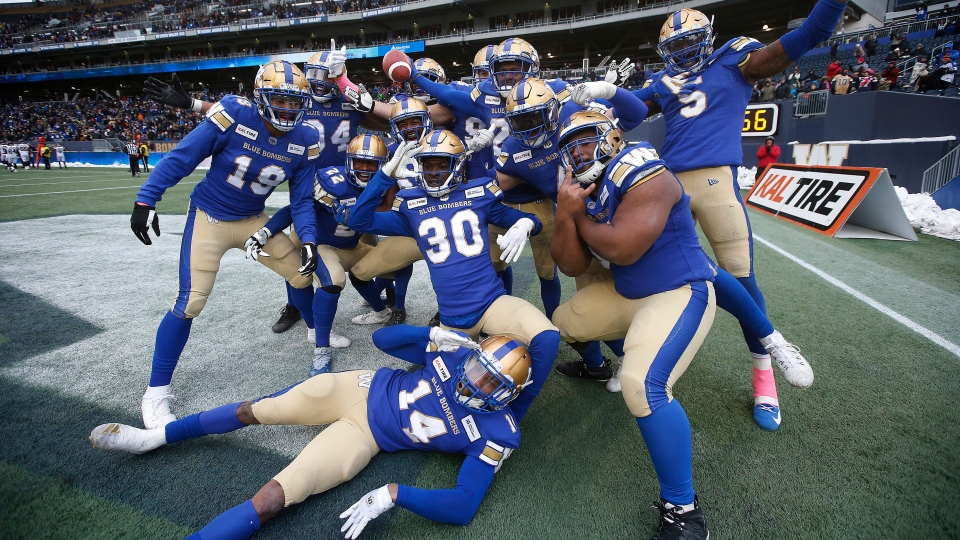 Winnipeg Blue Bombers' Nick Taylor (25), holding ball, and teammates celebrate his interception and touchdown during the second half of CFL action against the Montreal Alouettes, in Winnipeg, Saturday, Oct. 12, 2019. (THE CANADIAN PRESS/John Woods)