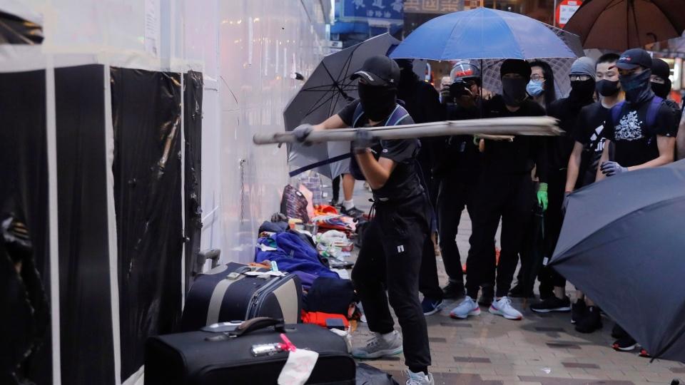 Protestors damage a wall of Bank of China in Hong Kong, Sunday, Oct.13, 2019. (AP Photo/Kin Cheung)