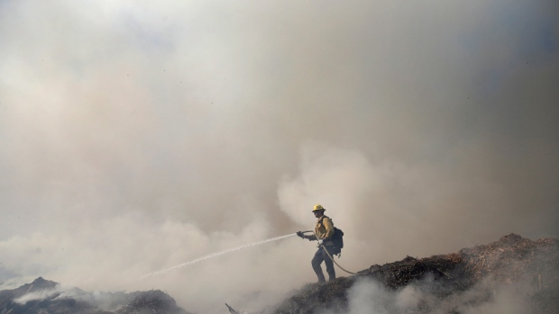 Randy Lenain, a firefighter with the Los Angeles Fire Department, works on containing a wildfire at an organic soils and mulch plant Saturday, Oct. 12, 2019, in Newhall, Calif. (AP Photo/Marcio Jose Sanchez)