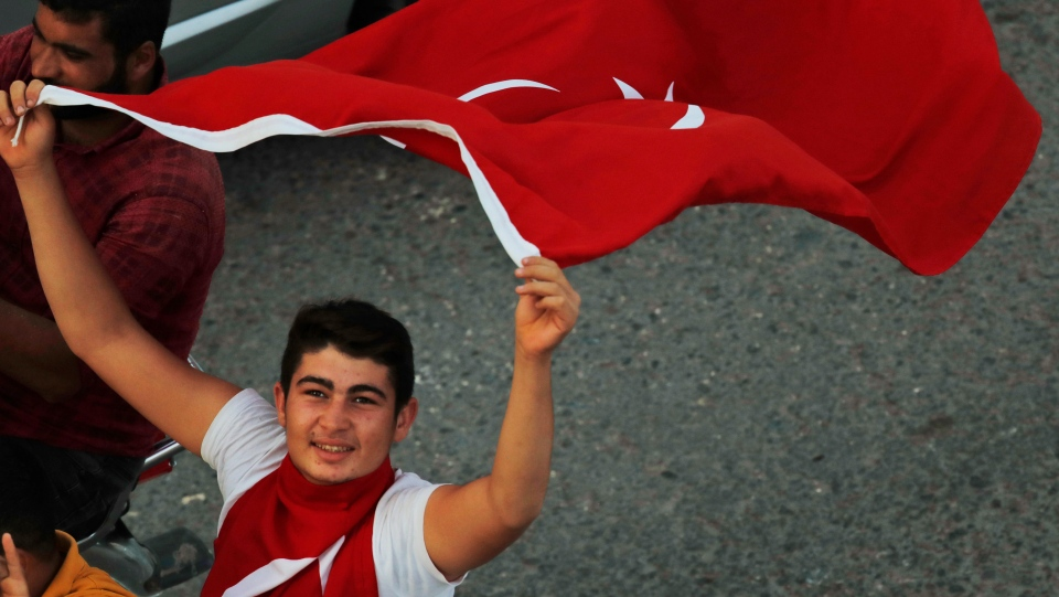 Youths celebrate in Akcakale, Sanliurfa province, southeastern Turkey, after the state-run Anadolu news agency reported the northern Syrian town of Tal Abyad had fallen to a Turkish military offensive on Sunday, Oct. 13, 2019. (AP Photo/Lefteris Pitarakis)