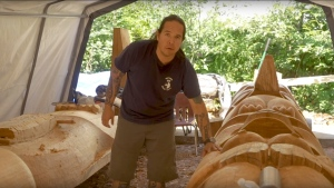 Heiltsuk carver Ian Reid shows one of the locally sourced and milled cedar logs that will make up the Big House. (Heiltsuk Nation)