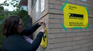 Election worker Shadoe Ball tapes a sign pointing towards an advance voting poll station in the electoral district of Toronto Centre at Muriel Collins Housing Cooperative in Toronto on Friday Oct. 11, 2019. THE CANADIAN PRESS/Doug Ives