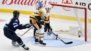 Pittsburgh Penguins' Zach Aston-Reese (46) scores a short-handed goal on Winnipeg Jets' goaltender Laurent Brossoit (30) during third period NHL action in Winnipeg on Sunday, Oct. 13, 2019. (THE CANADIAN PRESS/Fred Greenslade)