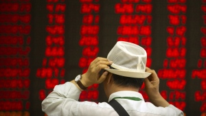 An investor adjusts his hat as he monitors stock prices at a brokerage house in Beijing, on Sept. 5, 2019. (Mark Schiefelbein / AP)