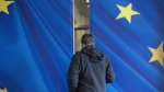 A man walks through a sliding door with the European Union stars outside EU headquarters in Brussels, on Oct. 13, 2019. (Virginia Mayo / AP)