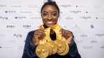 Simone Biles of the United States shows her five gold medals at the Gymnastics World Championships in Stuttgart, Germany, Sunday, Oct. 13, 2019. (Marijan Murat/dpa via AP)