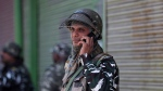An Indian paramilitary soldier talks on his cellphone as he guards a closed market in Srinagar, Indian controlled Kashmir, Monday, Oct. 14, 2019. Postpaid cellphone services were restored in India-administered Kashmir on Monday, more than two months after India's government downgraded the region's semi-autonomy and imposed a security and communications lockdown. (AP Photo/Mukhtar Khan)