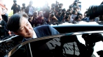 South Korean Justice Minister Cho Kuk gets into a car to leave the Gwacheon Government Complex in Gwacheon, South Korea, Monday, Oct. 14, 2019. Cho on Monday offered to step down amid an investigation into allegations of financial crimes and academic favors surrounding his family, a scandal that has rocked Seoul's liberal government and deeply polarized national opinion. (Shu Myung-gon/Yonhap via AP)