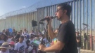 Choir! Choir! Choir! co-founder Nobu Adilman speaks with the crowd at the Mexican border town of Tijuana on Oct. 13, 2019. (Facebook choirx3)