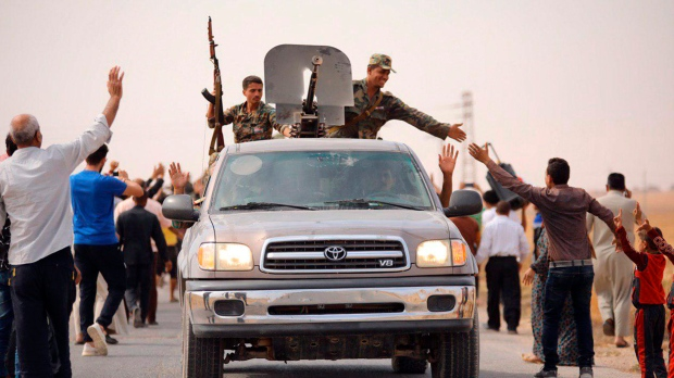 In this photo released by the Syrian official news agency SANA, people welcome Syrian troops as they enter the town of Ein Issa, north of Raqqa, Syria, Monday, Oct 14, 2019. Syrian troops moved east from Aleppo province to Raqqa where state media said they had reached Ein Issa. (SANA via AP)