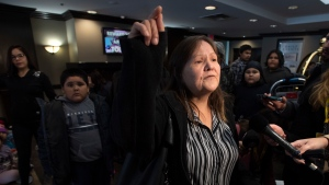 Surrounded by evacuees, Margaret Missyabit, an evacuated member of the Lake Manitoba First Nation speaks with the media at a hotel in Winnipeg, Monday October 14, 2019. THE CANADIAN PRESS/Adrian Wyld