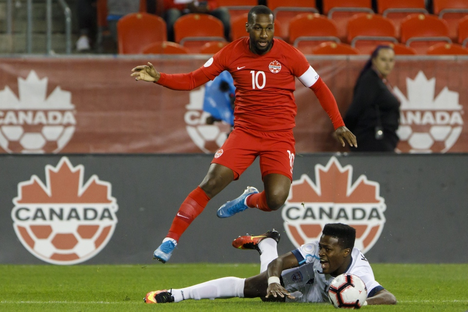 Canada forward Junior Hoilett (10) leaps over Cuba defender Karel Espino (14) during first half CONCACAF Nations League play at BMO Field in Toronto, Saturday, Sept. 7, 2019. THE CANADIAN PRESS/Cole Burston
