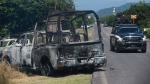 A charred truck that belongs to Michoacan state police sits on the side of the road after it was burned during an attack, as state police drive past in El Aguaje, Mexico, Monday, Oct. 14, 2019. (AP Photo/Armando Solis)