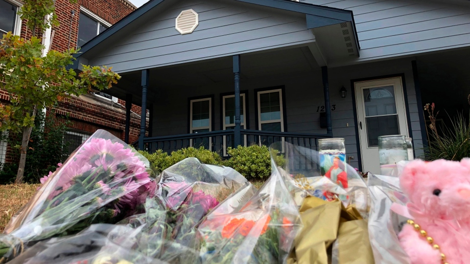Bouquets of flowers and stuffed animals are piling up outside the Fort Worth home Monday, Oct. 14, 2019, where a 28-year-old black woman was shot to death by a white police officer. (AP Photo/Jake Bleiberg)