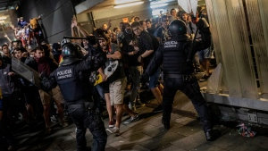 Police clash with protesters during a demonstration at El Prat airport, outskirts of Barcelona, Spain, Monday, Oct. 14, 2019. (AP Photo/Bernat Armangue)