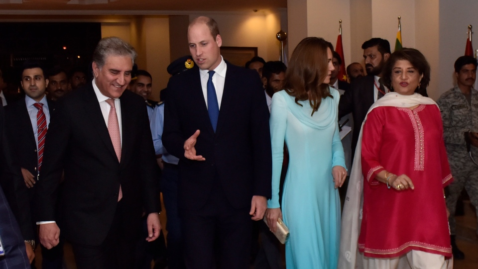 In this picture released by the Foreign Office, Pakistan's Foreign Minister Shah Mahmood Qureshi, left, escorts Britain's Prince William and his wife Kate as they arrive at the Nur Khan base in Islamabad, Pakistan, Monday, Oct. 14, 2019. (Pakistan Foreign Office via AP)