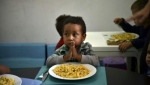 A child prays before eating at the Kapuy Foundation shelter which supports children abandoned, or with serious health problems, including undernourishment in Venezuela. (AFP)
