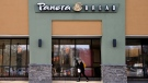 In this Wednesday, April 12, 2017, file photo, a passer-by walks near an entrance to a Panera Bread restaurant in Natick, Mass. (AP Photo/Steven Senne, File)