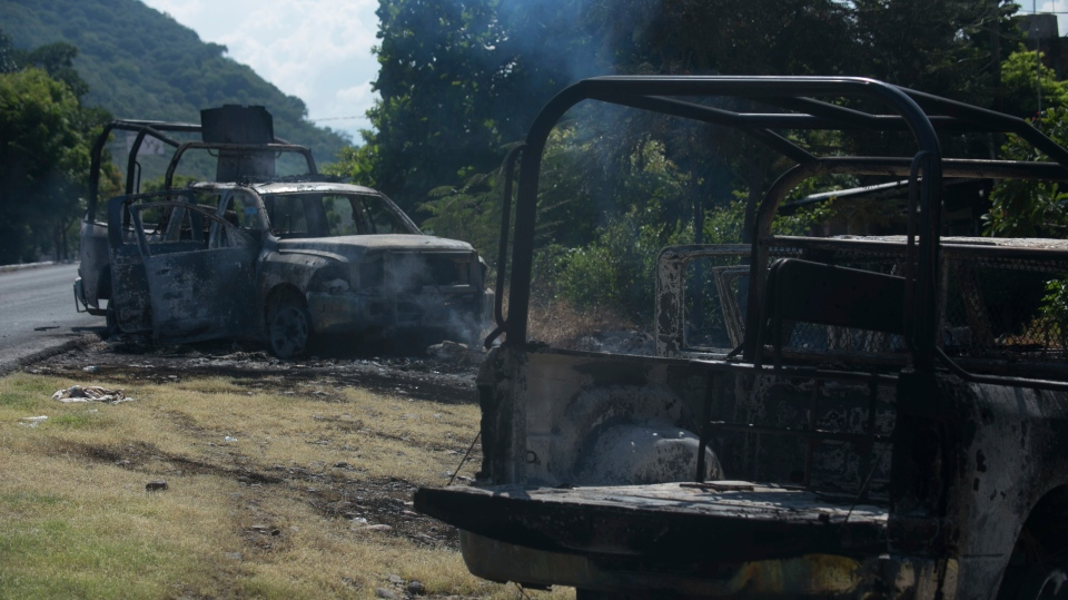 Charred trucks that belong to the Michoacan state police stand on the roadside after they were attacked in El Aguaje, Mexico, Monday, Oct. 14, 2019. At least 13 police officers were killed and nine others injured in the ambush. (AP Photo/Armando Solis)