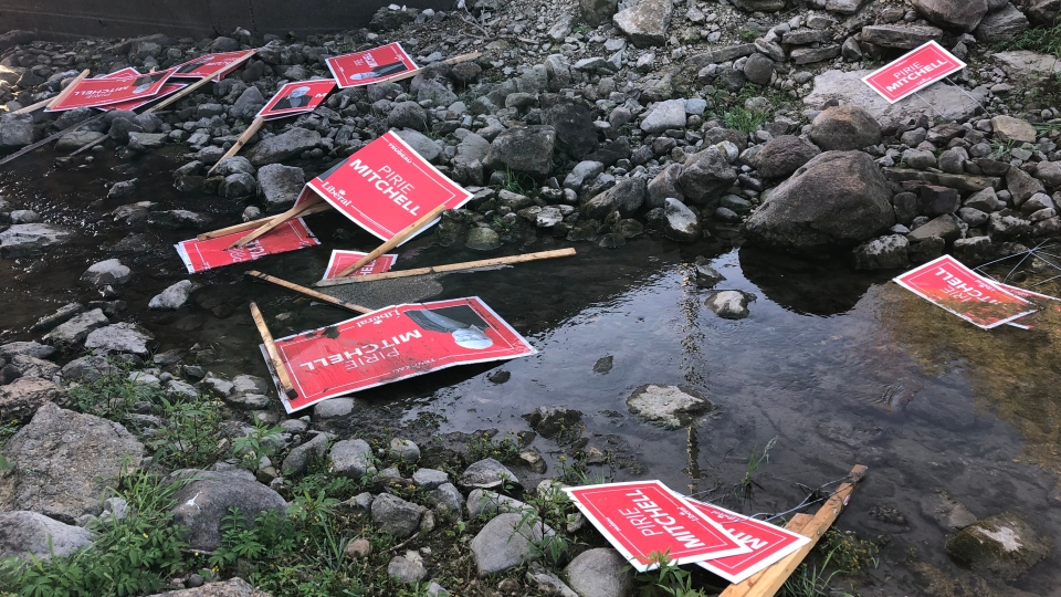 A number of election signs under a bridge