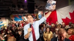Federal Liberal leader Justin Trudeau holds up the party platform at a rally in Ottawa on Friday October 11, 2019. THE CANADIAN PRESS/Frank Gunn