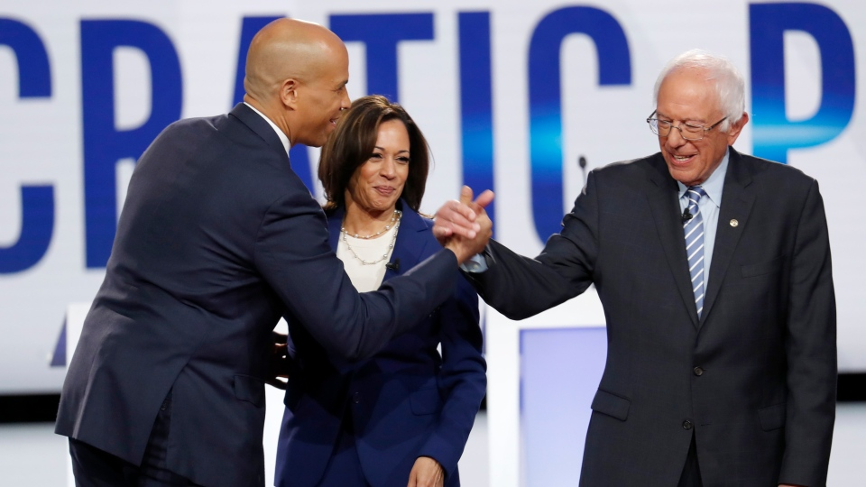 U.S. Democratic presidential candidate Sen. Cory Booker, D-N.J., left, Sen. Kamala Harris, D-Calif., and Sen. Bernie Sanders, I-Vt., right, greet each other on stage ahead of a Democratic presidential primary debate hosted by CNN and The New York Times at Otterbein University, Tuesday, Oct. 15, 2019, in Westerville, Ohio. (AP Photo/John Minchillo)