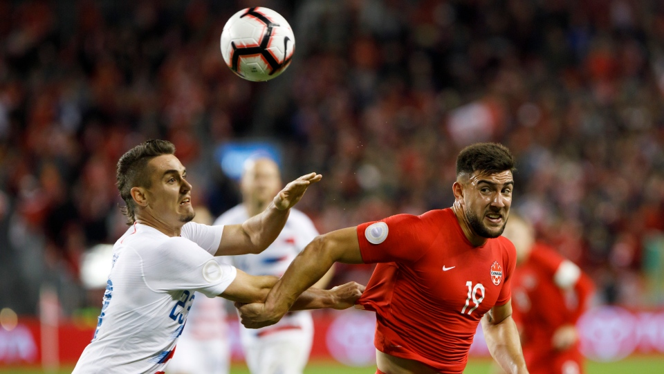 United States defender Aaron Long (23) and Canada forward Lucas Cavallini (19) battle for the ball during second half of CONCACAF Nations League soccer action in Toronto, Tuesday, Oct. 15, 2019. THE CANADIAN PRESS/Cole Burston