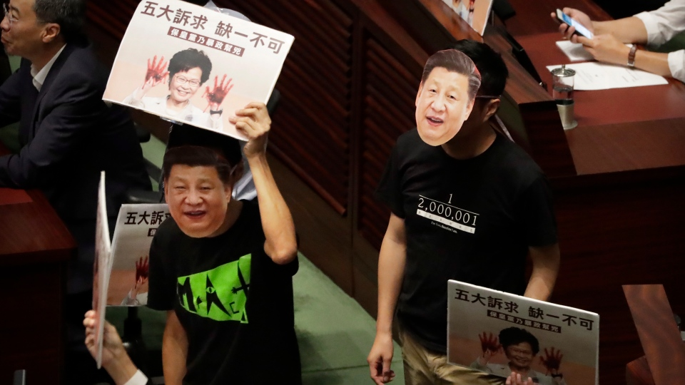 Pan-democratic legislators wearing masks of Chinese President Xi Jinping protest as Hong Kong Chief Executive Carrie Lam attempts to give a policy speech at the Legislative Council in Hong Kong, Wednesday, Oct. 16, 2019. (AP Photo/Mark Schiefelbein)