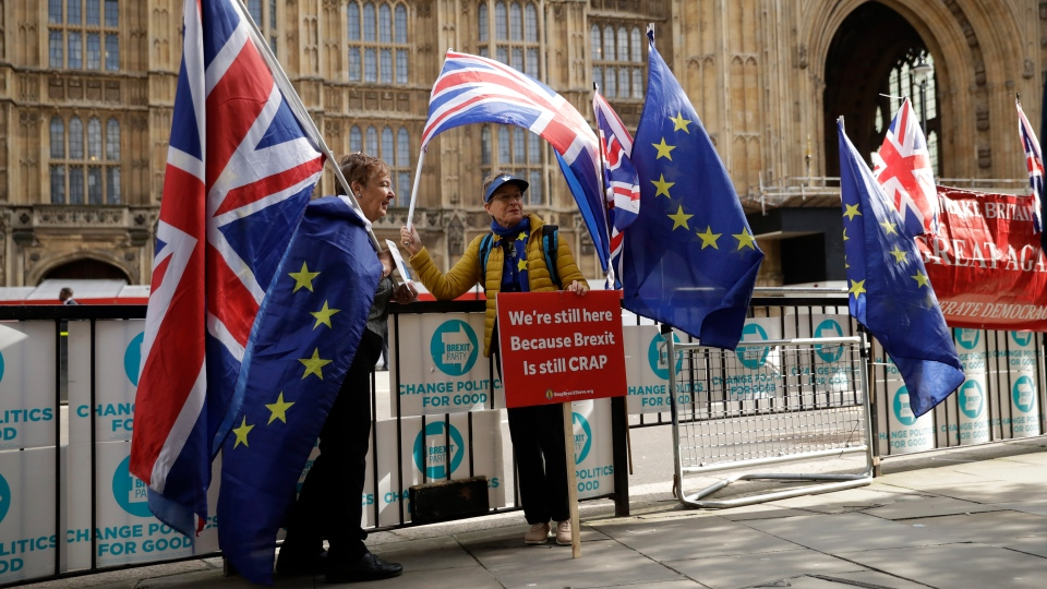 Anti-Brexit remain in the European Union supporters protest across the street from the Houses of Parliament in London, Tuesday, Oct. 15, 2019. (AP Photo/Matt Dunham)