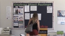 A woman reviews the ads on a job posting board (file)