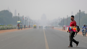 India's Presidential Palace, in the backdrop, is covered with smog as as a roadside vendor crosses Rajapth, the ceremonial boulevard in New Delhi, India, Wednesday, Oct. 16, 2019. (AP Photo/Altaf Qadri)