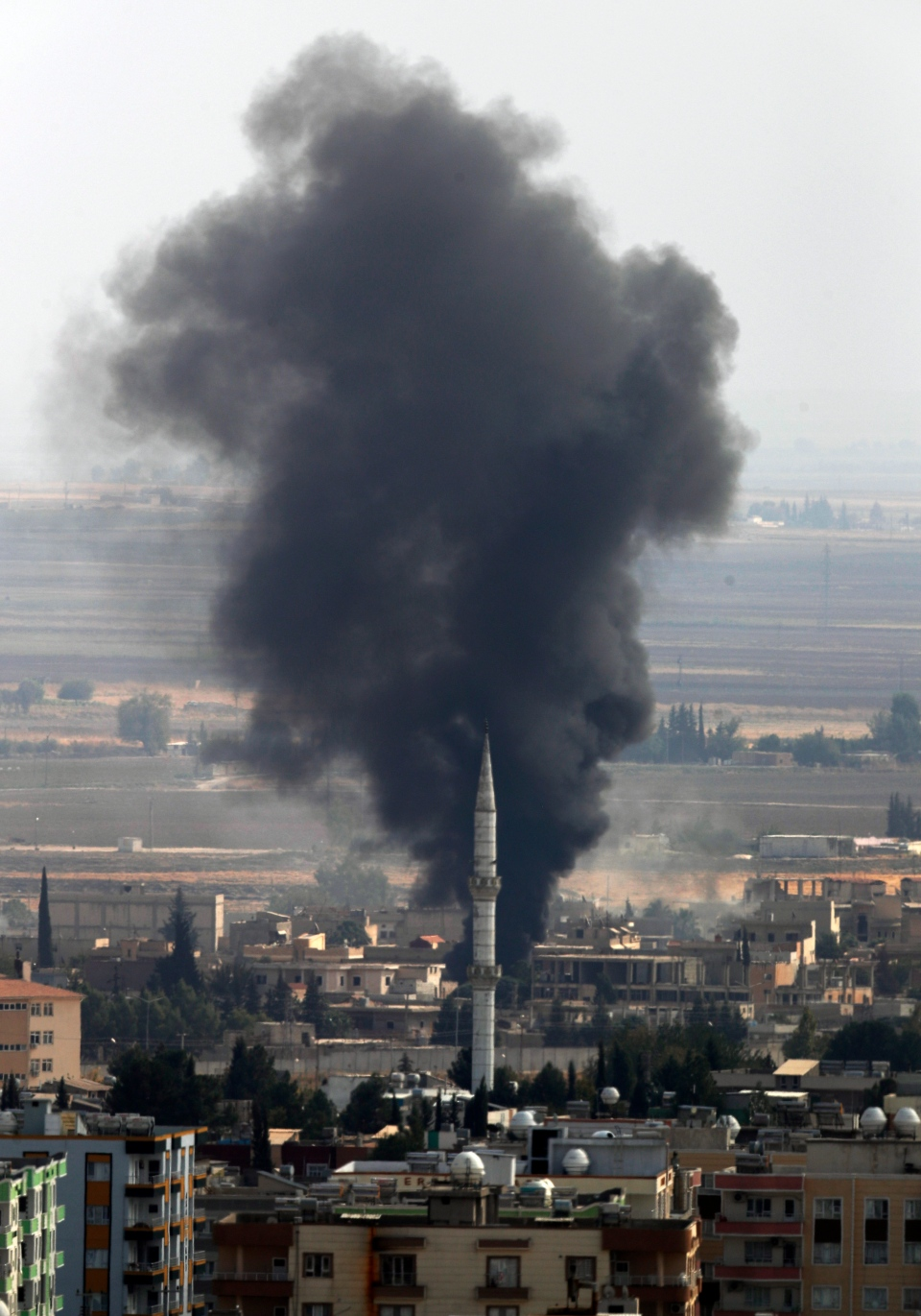 In this photo taken from the Turkish side of the border between Turkey and Syria, in Ceylanpinar, Sanliurfa province, southeastern Turkey, smoke billows from a target behind a mosque's minaret in Ras al-Ayn, Syria, during bombardment by Turkish forces, Wednesday, Oct. 16, 2019. (AP Photo/Lefteris Pitarakis)