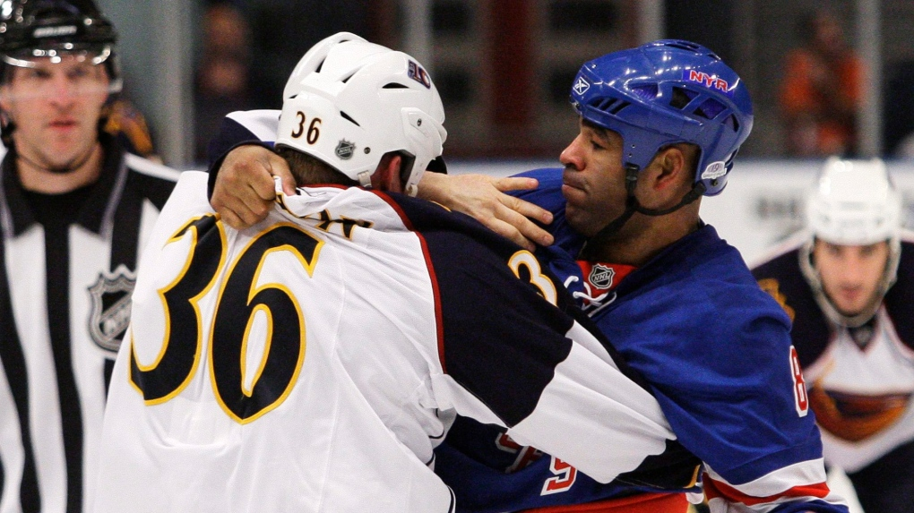 Former NHL enforcer Donald Brashear helping hockey friend Pierre Sevigny run a Tim Hortons